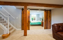 Sliding barn doors bring both living space and bedroom space in Minneapolis basement remodel.