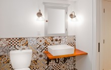 Eclectic tile installation in Minneapolis basement bathroom with vessel sink.